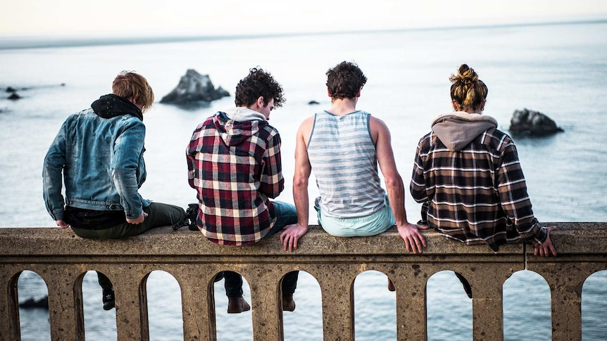 Four men sit along a bridge with their backs facing the camera