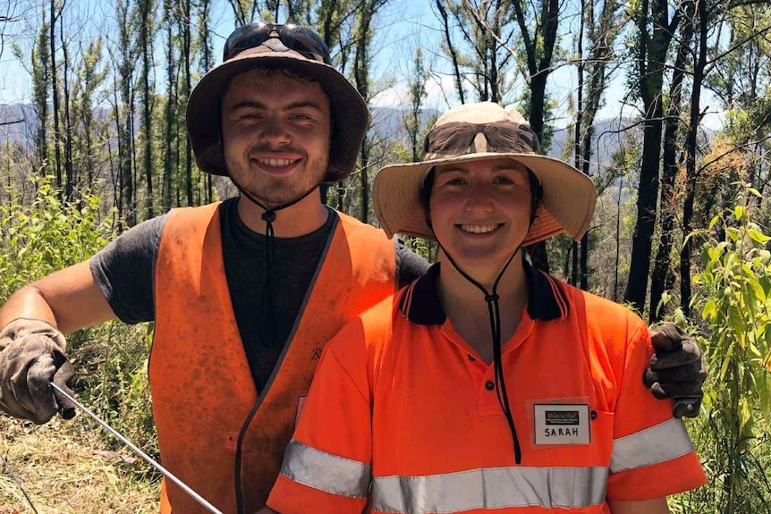 Two people in work clothes and hats standing in front of a fence.