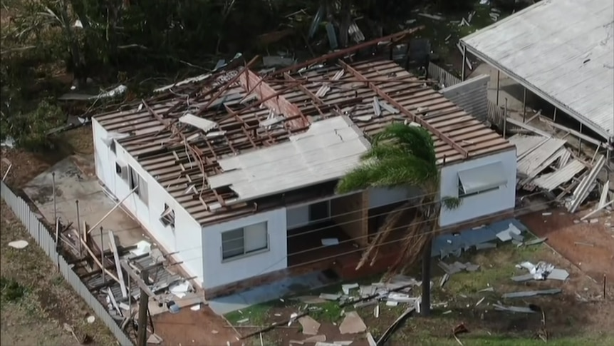 A drone aerial photo of a house with its roof destroyed and debris all around on the ground.
