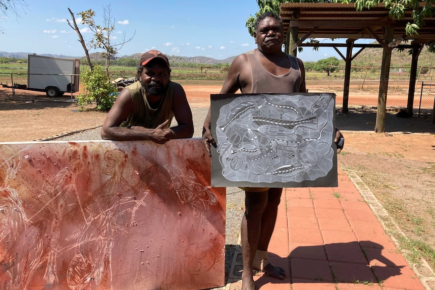 Shaun Namarnyilk and Gabriel Maralngurra with recently finished artworks. They are outside, and there is red dirt and trees.