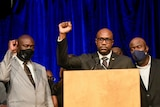 Two black men in suits and ties raise their right arms in triumph in front of blue curtain in room.