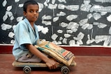 A 10-year-old Indian polio victim moves his wooden plank with wheels.