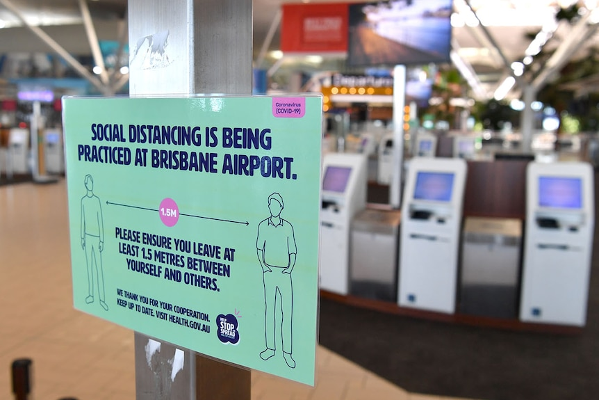 A sign encouraging social distancing near empty check-in counters at Brisbane International Airport.