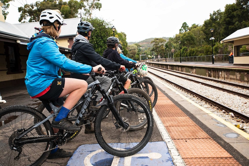 A group of teenagers sit on their bikes on a railway station platform.