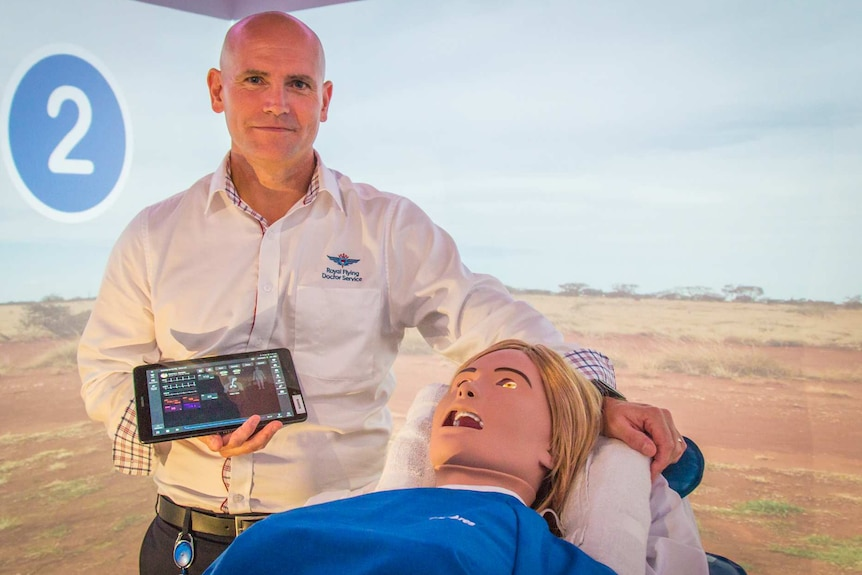 Man with a medical dummy holding an iPad with a video of the outback behind him.