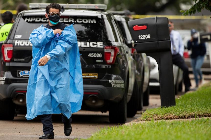 Seorang petugas medis dari Departemen Pemadam Kebakaran Houston melepas lapisan alat pelindung diri setelah meninggalkan lokasi kasus penyelundupan manusia.
