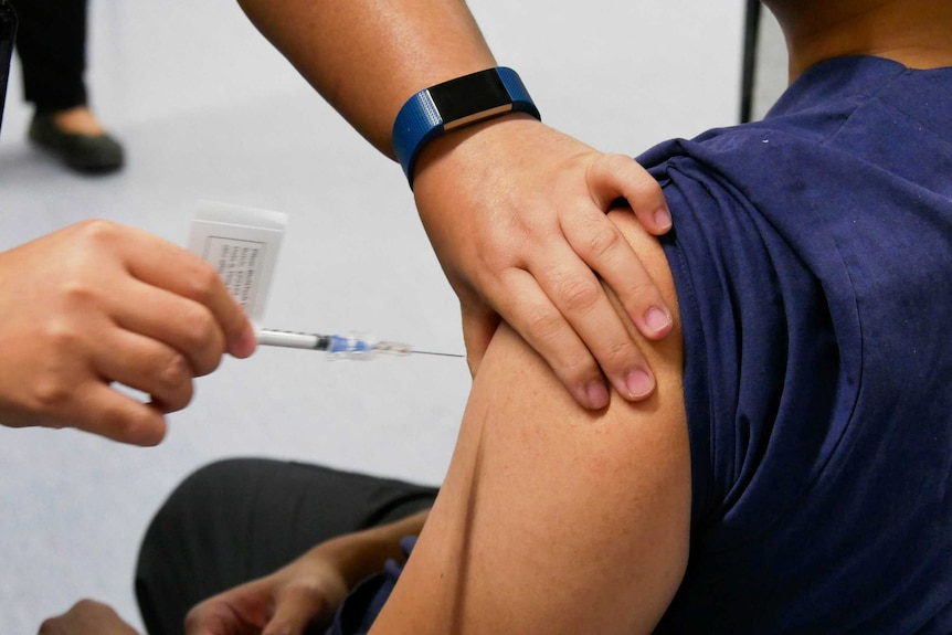 A person administers a vaccine