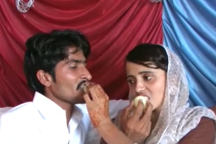 A woman in a veil feeds a man cake while he feeds her cake