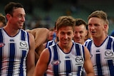 North Melbourne Kangaroos players smile as they walk off the field after their first win of the 2021 AFL season.