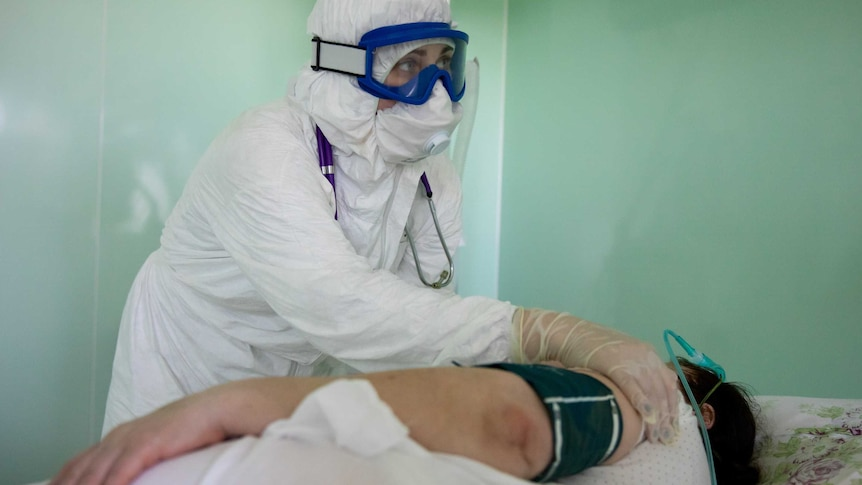 Health worker in white suit with blue goggles places hand on a patient