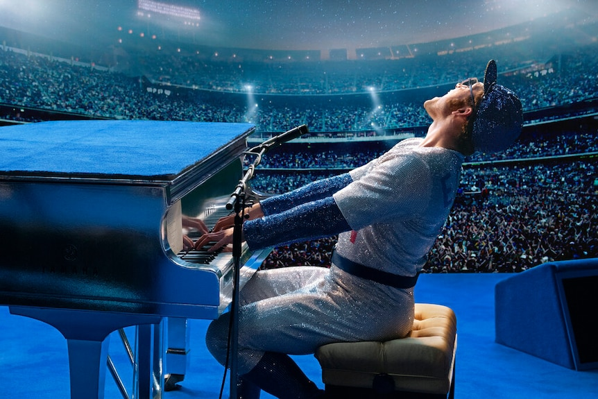 A man in a glittering suit plays a piano on stage