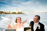 A laughing bride and groom on a boat in Sydney Harbour with the bridge behind them. She is trying to catch her veil in the wind.