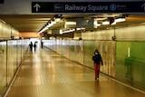 a woman walking through a tunnel