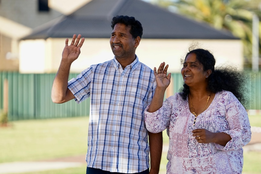 A man and woman wave while standing in a park