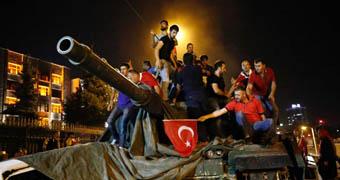People stand on a Turkish army tank in Ankara.