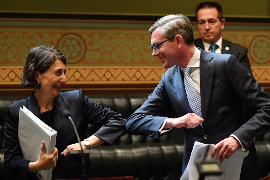 Gladys Berejiklian and Dominic Perrottet elbow bump in the Lower House.