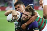 Melbourne Storm's Ryan Papenhuyzen dives for the tryline with South Sydney Rabbitohs' Latrell Mitchell around his neck.