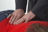 A chiropractor checking their patients back.