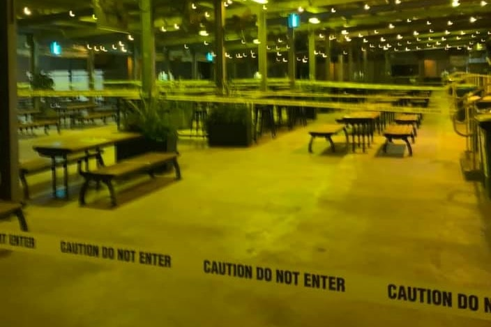 A dining area at a mining site, closed off with plastic tape that reads caution do not enter