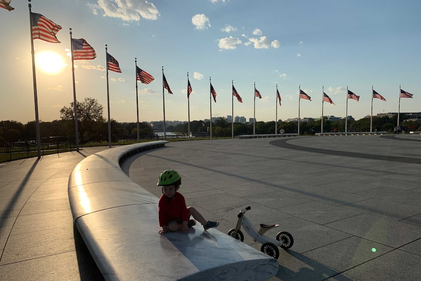 Little boy with bike and wearing bike helmet sitting on bench surrounded by American flags.