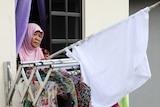 A woman wearing a headscarf stands with a white flag out the window of her apartment