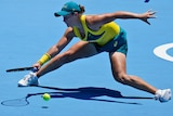 Ash Barty leans at full stretch to get her racquet to the ball during a point at the Olympics.