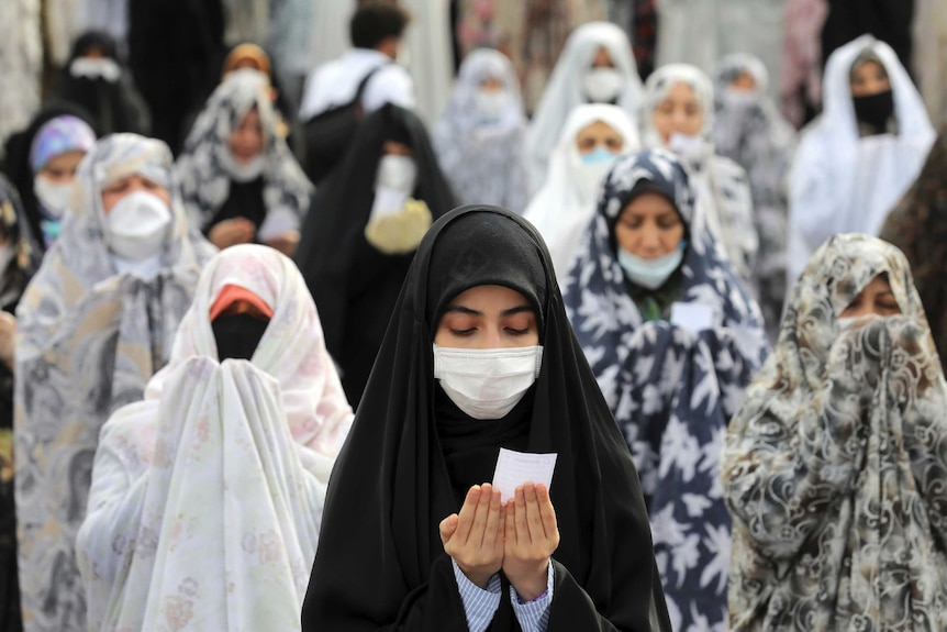 Women wear protective face masks and gloves as they pray in a mosque courtyard.
