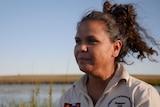 Aboriginal woman Madeline Anderson overlooking a waterhole and paddock at Yallalie Downs in Dandaragan.