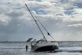 A rescue worker in the water beside a yacht washed up on a beach