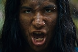 A sooty and muddy teen boy with long hair and nose and eyebrow piercing speaks with snarling and serious expression in jungle.