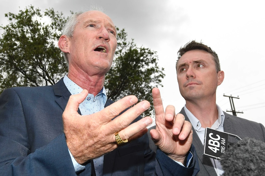 Steve Dickson gestures with his hands while James Ashby looks at him. The shot is from a low angle underneath the men.