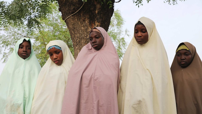 Five girls wearing long head scarfs stand next to a tree