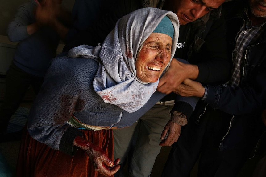 An older woman covered in blood cries as people try to comfort her.