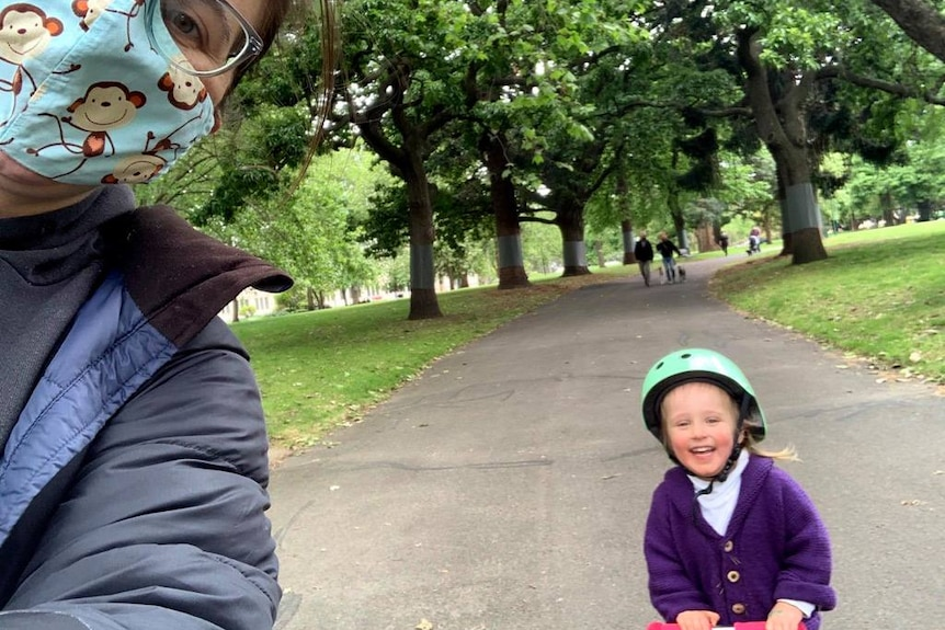 Woman wearing a mask takes a self with a child on a scooter.