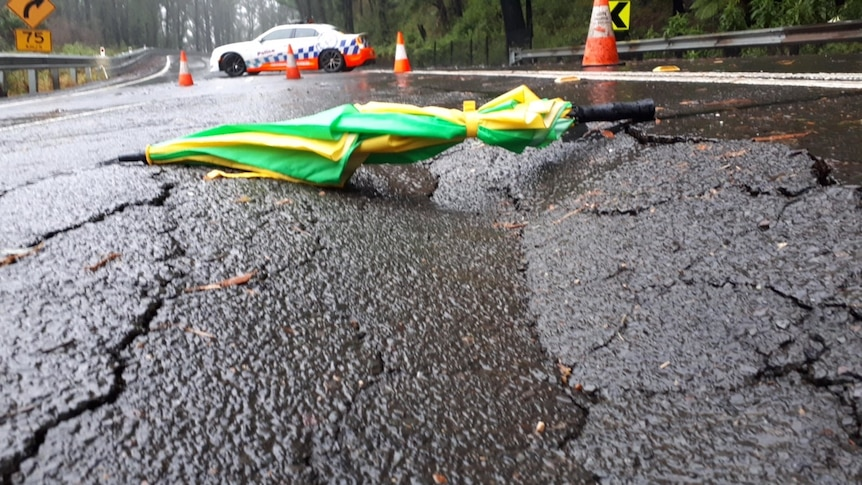 An umbrella lying over a depression in the road.