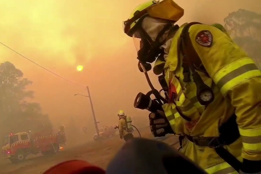 a person  in protective gear with a mask sating in the middle of smoke