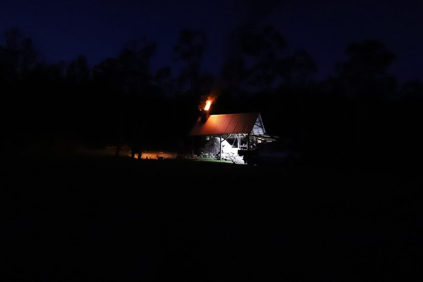 A bush shed with flames showing from a kiln.
