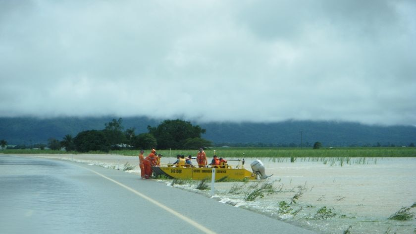 SES workers in floodboat alongside flooded Bruce Highway, searching for two men missing in floodwaters near Ingham.