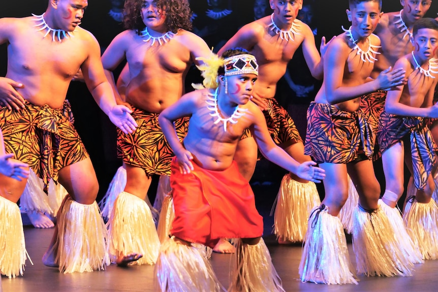 Young men in colourful Samoan clothing performing their fa'ataupati, or slap dance, a young boy out front