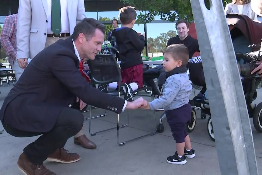 a man shaking a little child's hand