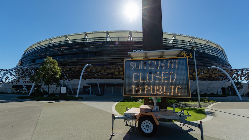 "A sign reading ""Sun event closed to public"" sits outside Optus Stadium before the AFL game between West Coast and Fremantle."