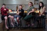 Four kids sit at a breakfast bar.