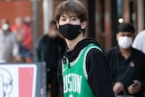A teenage boy wearing a mask and a bright green basketball jersey in the street