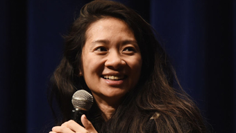 Chinese-American woman late 30s with long hair, smiling and holding mic, speaking.