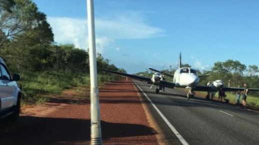 A small plane without damage sits in the middle of a highway in remote WA with people around it.