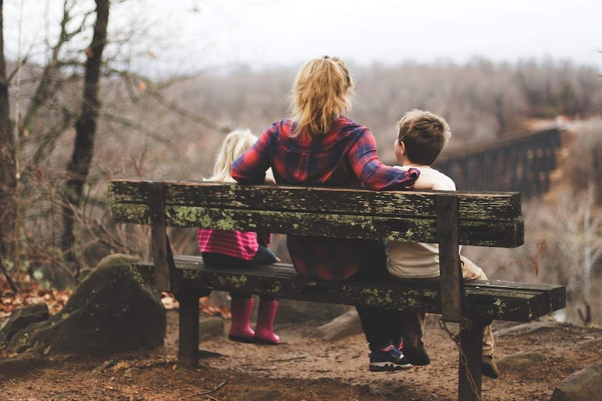 A woman sits on a park bench with her daughter and son.