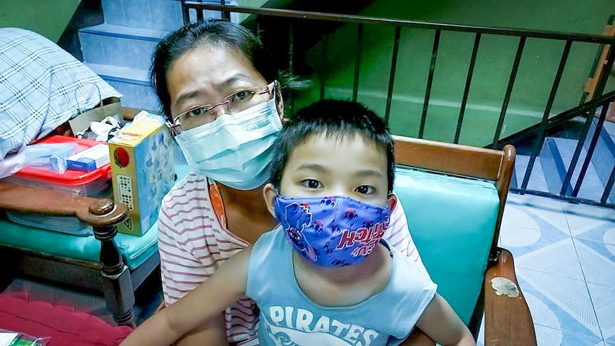 An older Thai woman in a face mask holds a small Thai boy, also in a mask, on her lap