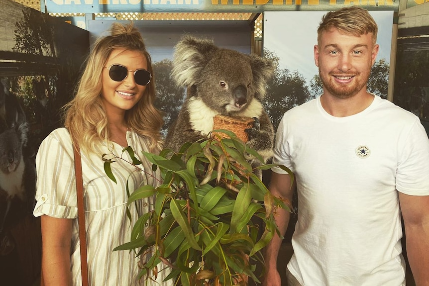 A man with blonde hair together with a woman with blonde hair and a koala.