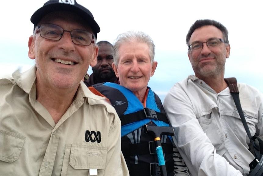 Three men in boat smiling at camera.