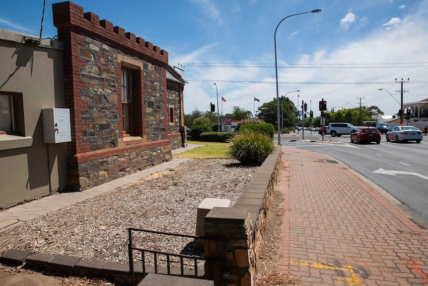 A bluestone wall fronts an intersection where cars wait at a traffic light.